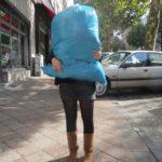 Frau trägt großen Müllsack, der ihr Gesicht verdeckt