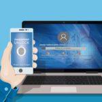 Hand hält Smartphone vor Laptop mit Anmeldemaske