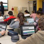 Schulklasse arbeitet mit Laptops und Smartboard