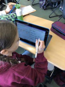 Schülerin schreibt mit Active Pen auf dem Display ihres Laptops
